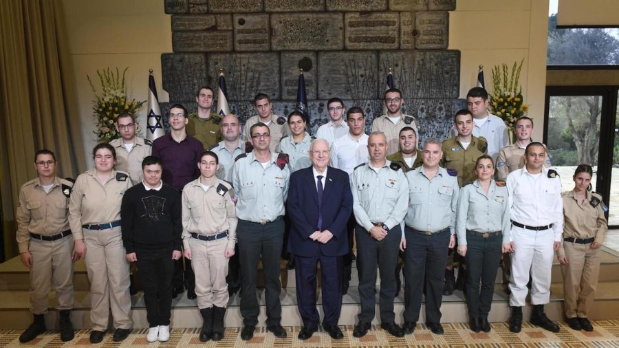 Israeli President Rivlin and Special in Uniform soldiers smile together in front of Israeli flags, standing on steps
