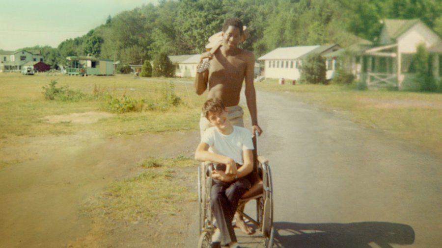 Neil Jacobson, sitting in a manual wheelchair, and Alan Ford at Camp Jened in 1968