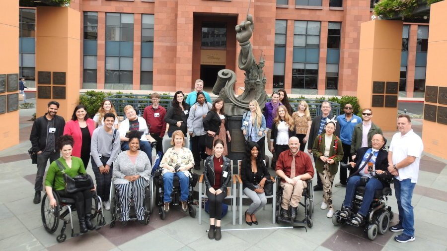 Summer Lab 2019 participants smile together around a statue of Mickey Mouse at The Walt Disney animation studios