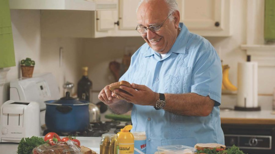A man in his kitchen holding bread and a knife, making a sandwich.