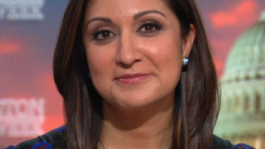 Amna Nawaz smiling headshot on the PBS NewsHour set.