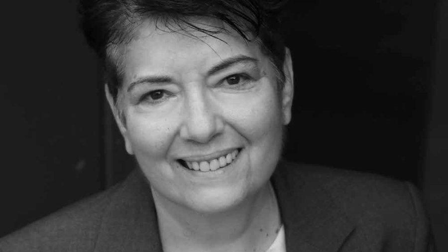 Angela Arena smiling headshot wearing a suit jacket
