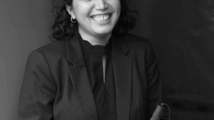 Baksha Ali smiling holding a white cane
