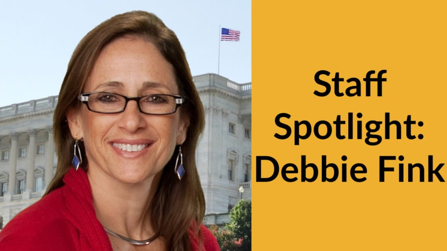 Debbie Fink smiling headshot in front of an American flag and a government building. Text: Staff Spotlight: Debbie Fink