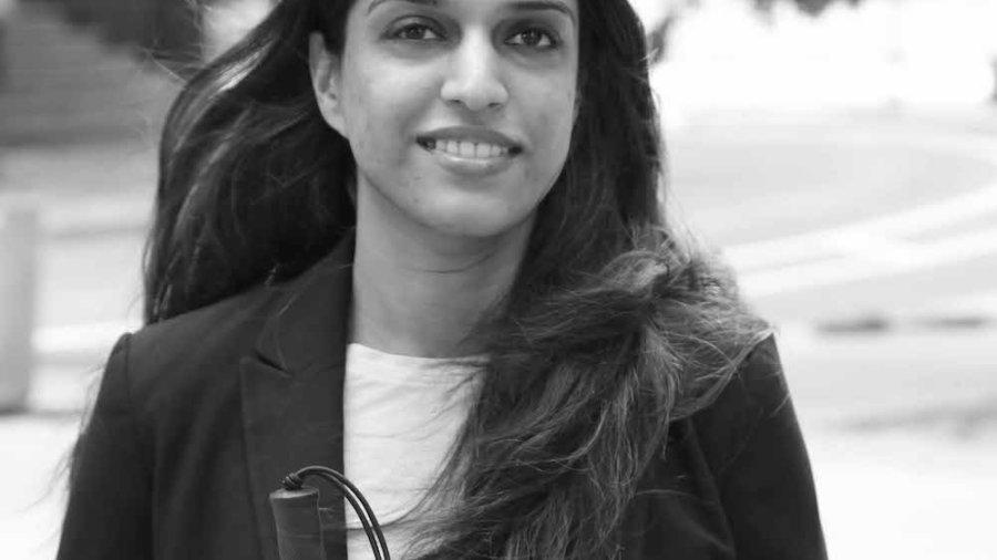 Khadija Bari walking down a street holding a white cane, smiling