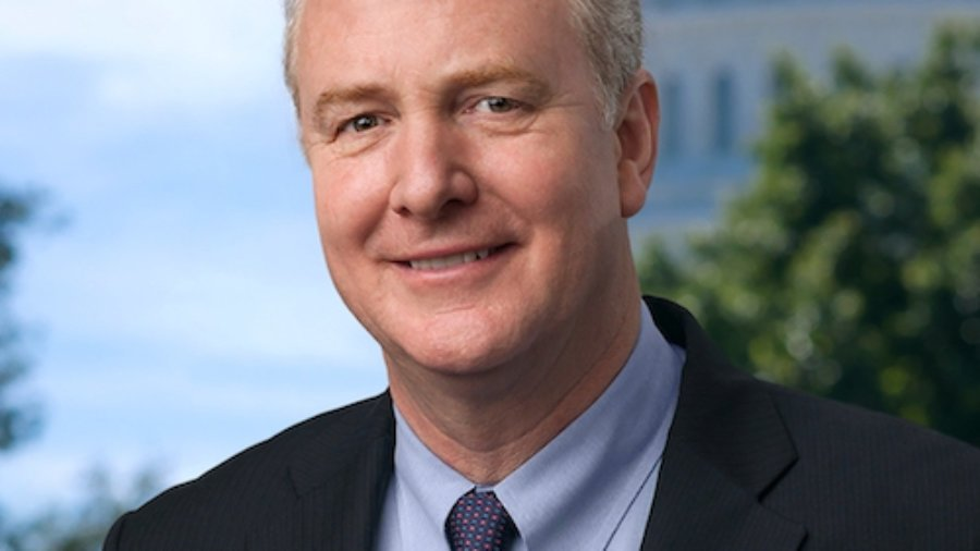 Chris Van Hollen smiling wearing a suit and tie with the US Capitol dome in the background behind him.