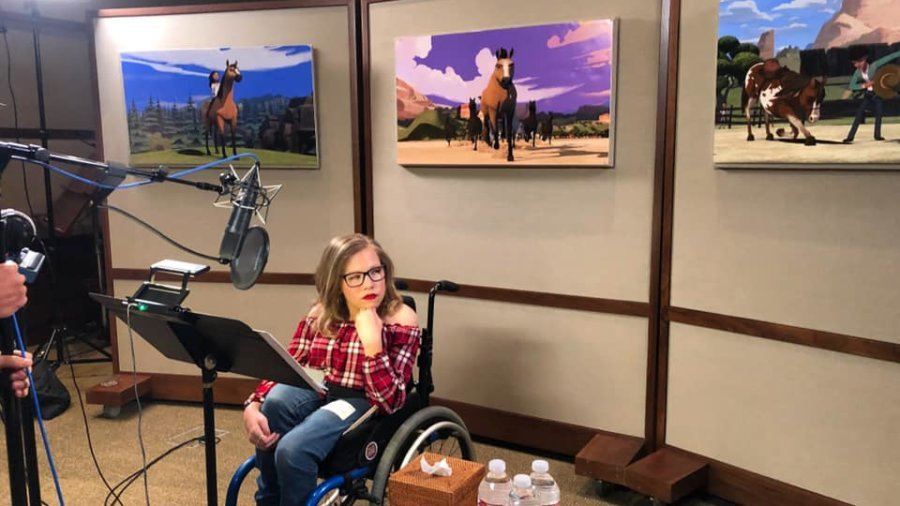 Cassidy Huff seated in her wheelchair in a recording studio