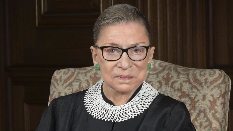 Justice Ruth Bader Ginsburg smiling wearing her robe, seated on a chair