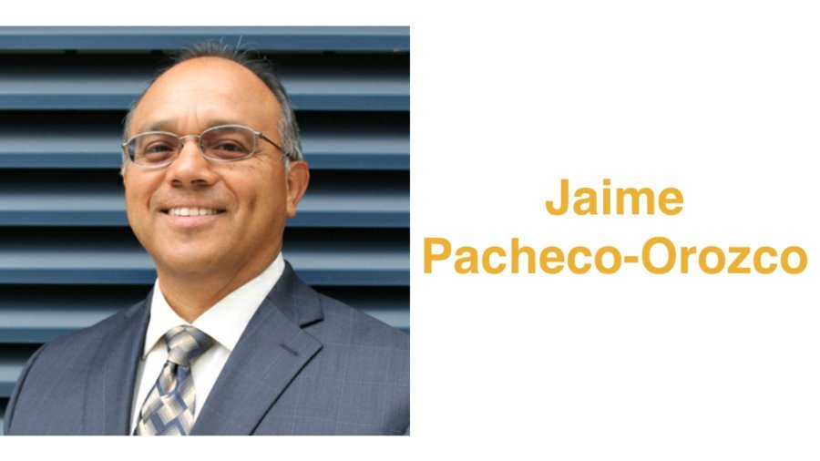 Jaime Pacheco Orozco smiling wearing a suit and tie and glasses. Jaime has short black hair. Text: Jaime Pacheco-Orozco