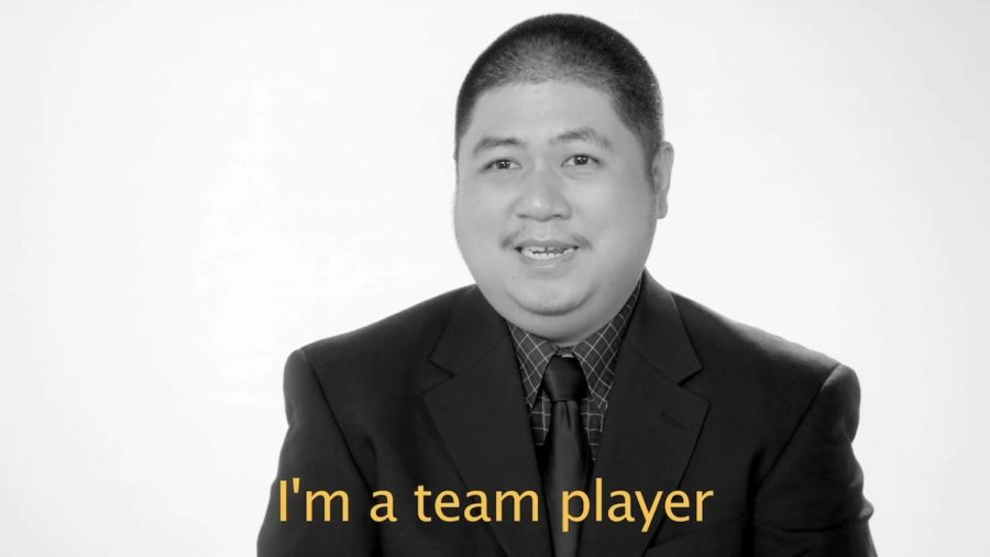 A man with a disability wearing a suit and tie speaking to camera in front of a white background. Caption: I'm a team player