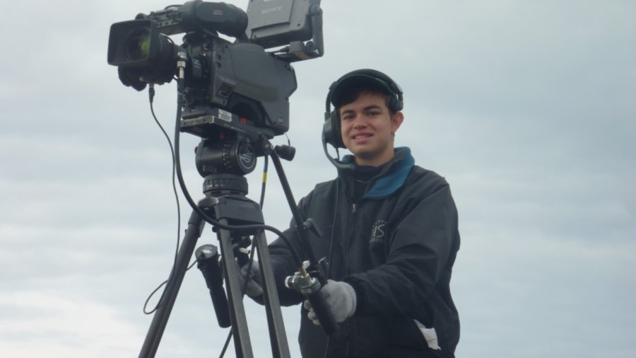 Ben Rosloff wearing a jacket and a headset standing behind a large video camera