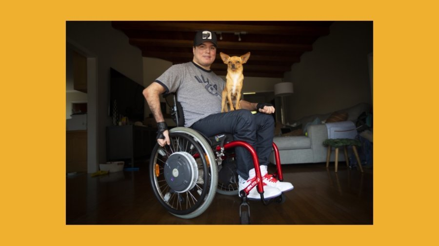 Roque Renteria with his dog on his lap. Roque is a wheelchair user.