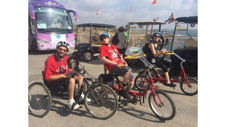 Blair Webb and two other participants on the birthright trip riding accessible bicycles in front of a large body of water
