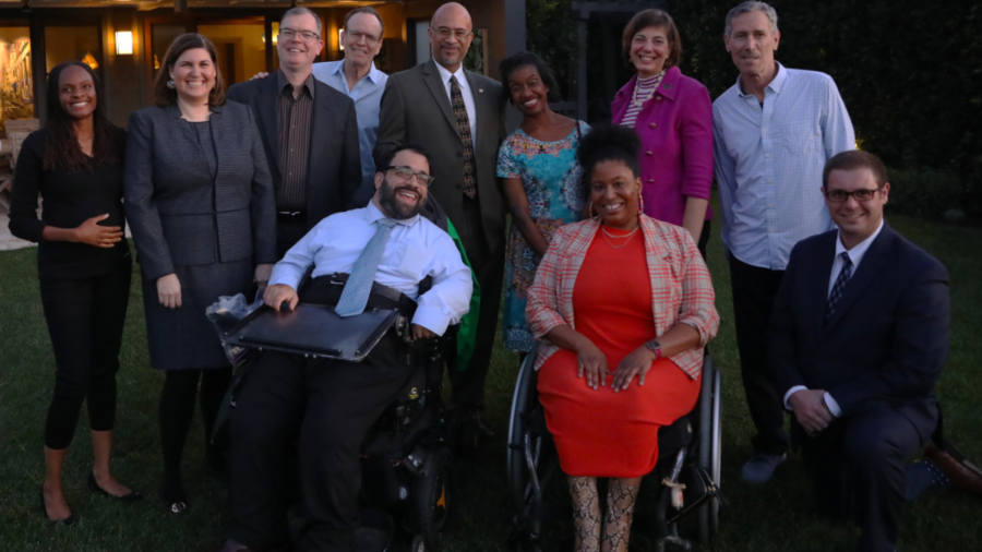 A group of diverse people with and without disabilities smiling together outside