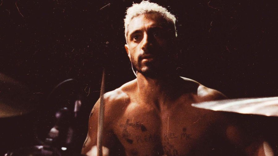 Riz Ahmed shirtless at a drum set in the poster for Sound of Metal