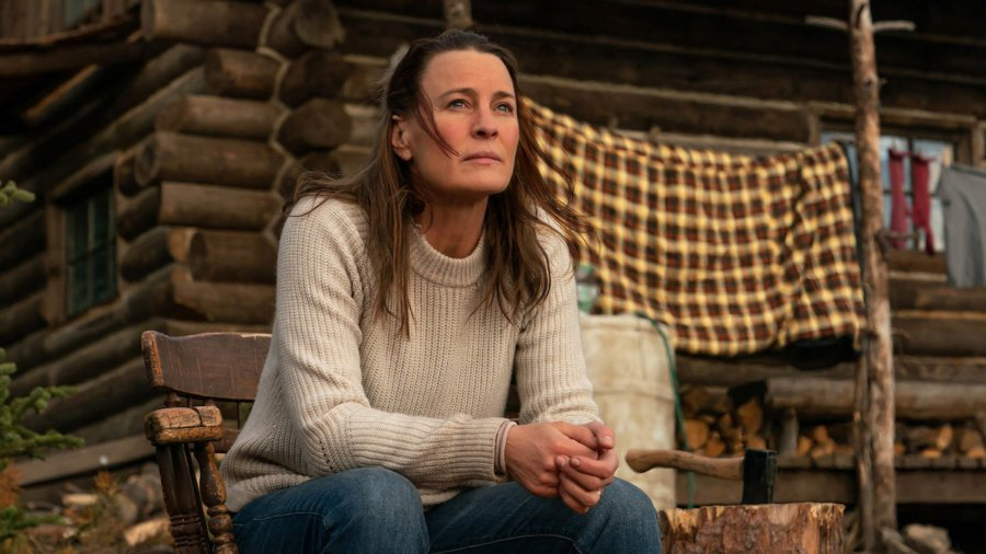 Robin Wright seated on a porch in a scene from Land