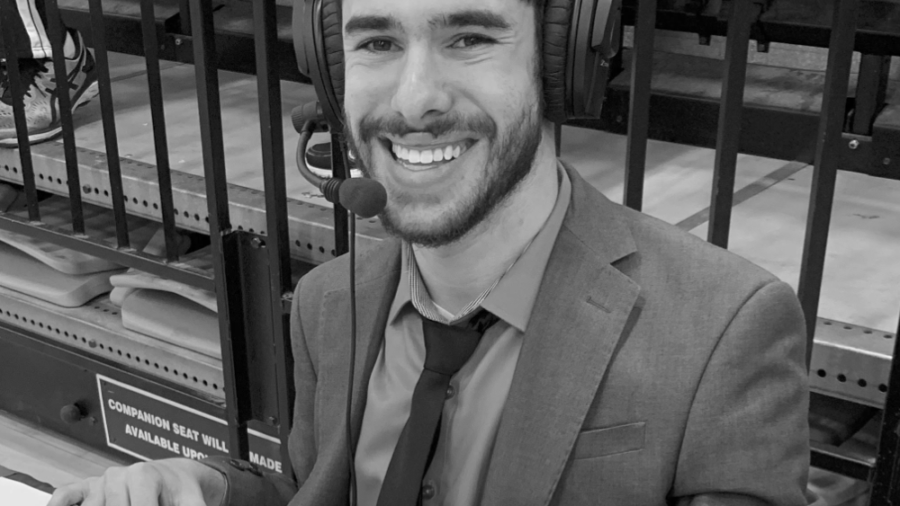 Justin Borses smiling wearing a headset and suit and tie while covering a game