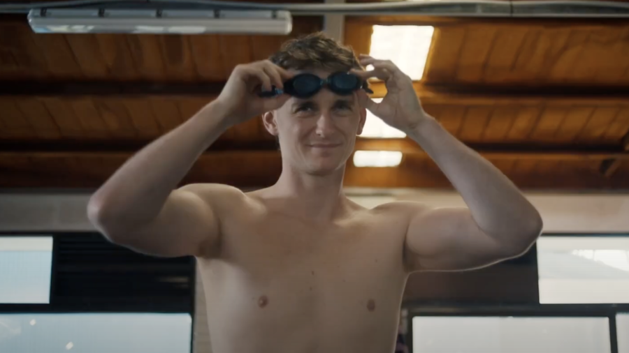 Adam Bowes as Alex putting on swim goggles in a scene from Diving In