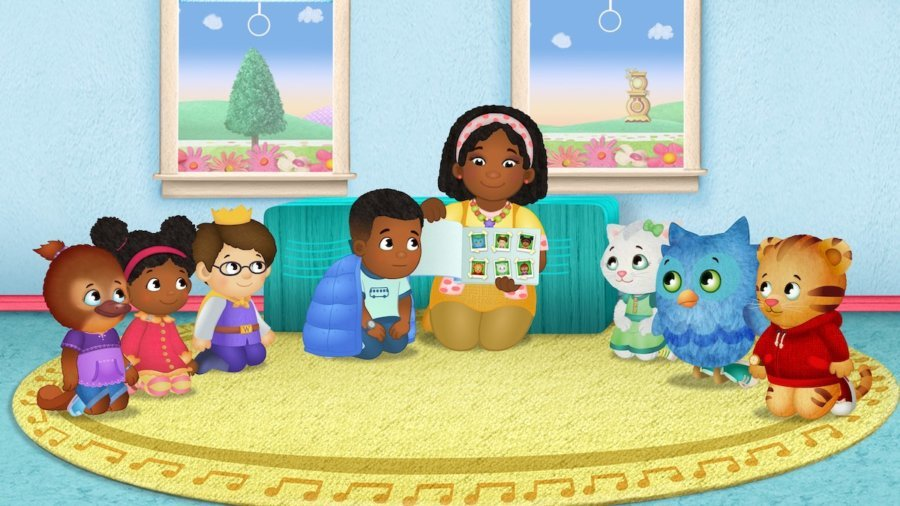 A scene from Daniel Tiger's Neighborhood with Max and all of the o there characters on a rug listening to a story