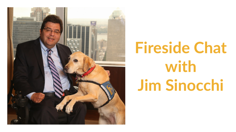 Jim Sinocchi sitting with a service dog in front of a window with skyscrapers behind him. Text: Fireside Chat with Jim Sinocchi