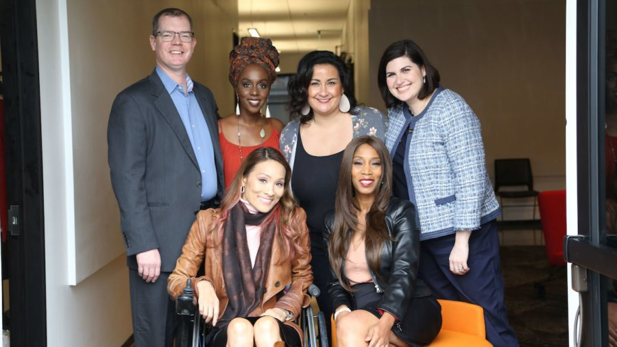 Six diverse people with disabilities smiling together inside a hallway