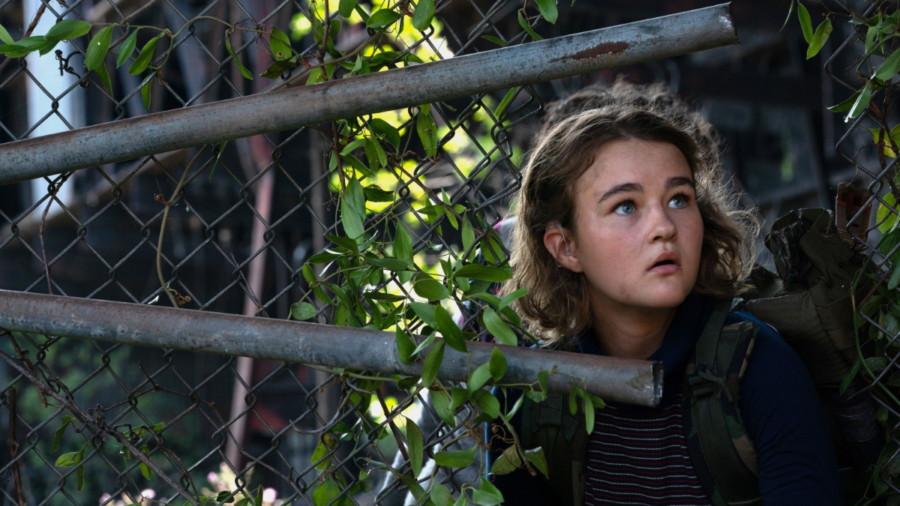 Millicent Simmonds in the woods behind a fence in a scene from A Quiet Place Part II