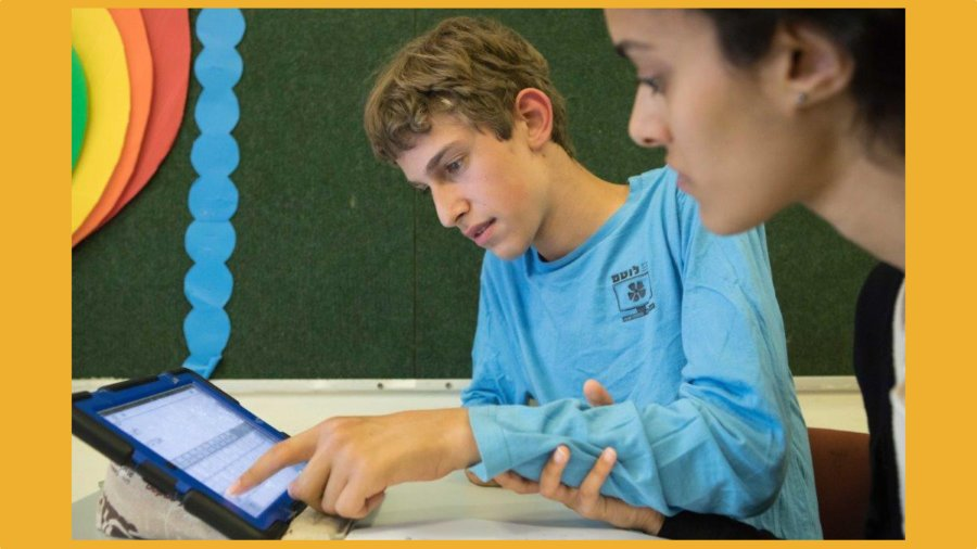 A boy with a disability and a teacher use an iPad together in a classroom