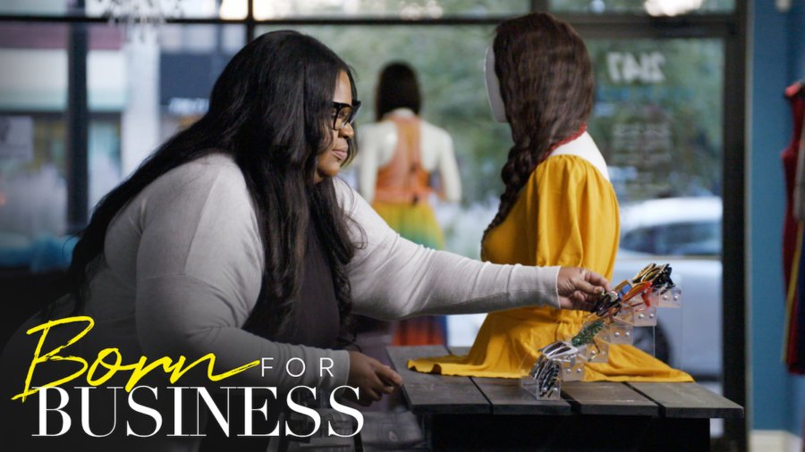 Qiana Allen working inside Cultures Closet. Born For Business logo in bottom left.
