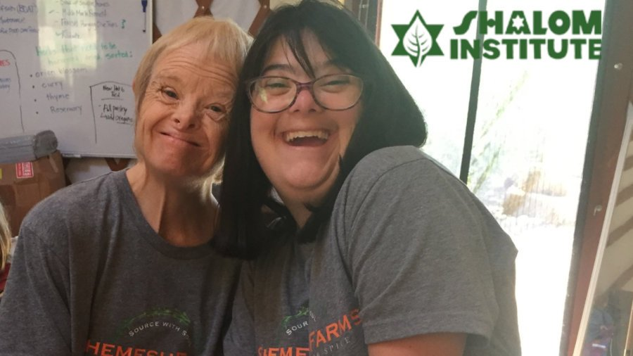 Two people with disabilities smiling wearing Shemesh Farm t-shirts. Shalom Institute logo.